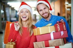 Happy couple in Santa hats Christmas shopping together.