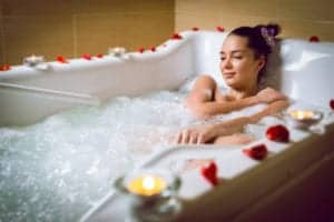 Woman relaxing in the tub at a Pigeon Forge hotel Jacuzzi suite.