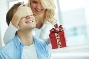Woman covering a man's eyes as she gives him a Christmas gift.