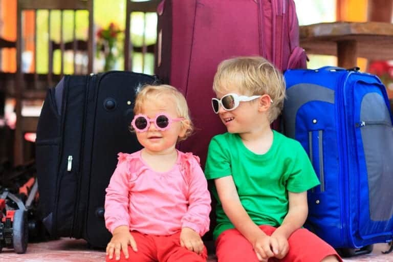 Young siblings wearing sunglasses sitting with luggage.