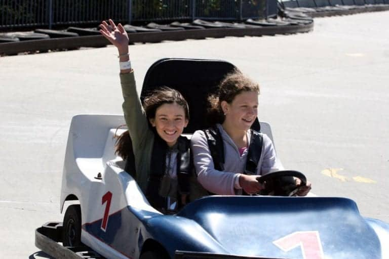 Two girls riding in a go kart.
