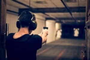 A man firing a gun at a shooting range.